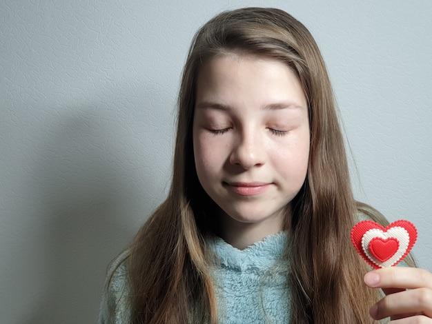 Portrait d'une adolescente avec un cœur dans sa main