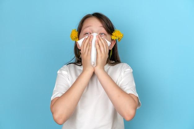 Portrait d'une adolescente avec un foulard blanc qui roule les yeux et éternue.