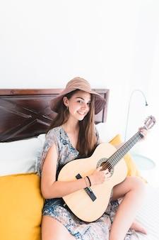 Portrait d'une adolescente heureuse assis sur un lit en jouant de la guitare