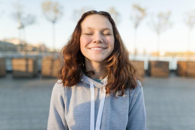 Portrait d'une adolescente heureuse avec les yeux fermés, heure d'or