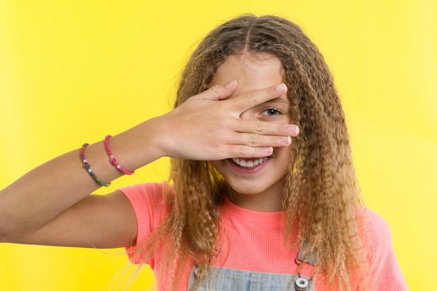 Portrait d'adolescente jette un coup d'oeil entre les doigts.