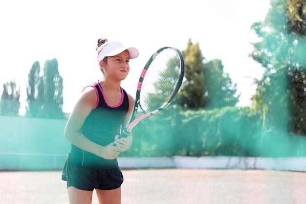 Portrait d'adolescente jouant au tennis sur un terrain de sport