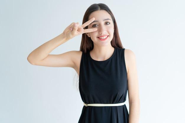 Portrait d'une adolescente joyeuse montrant le geste de paix