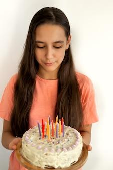 Portrait d'une adolescente latine joyeuse tenant un gâteau d'anniversaire avec une bougie. faire une fête de joyeux anniversaire à la maison. fond de mur blanc.