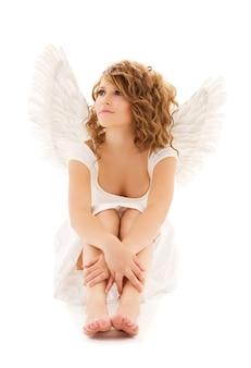 Portrait d'une adolescente malheureuse ange sur mur blanc