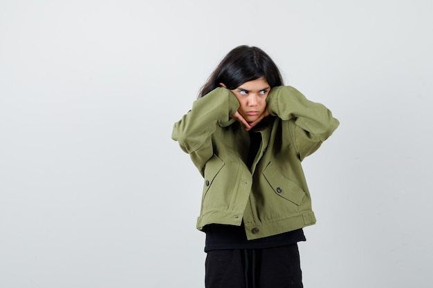 Portrait d'une adolescente mignonne boudant avec les joues appuyées sur les mains, regardant loin dans une veste verte de l'armée et regardant la vue de face pensive