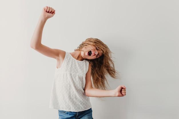 Portrait d'une adolescente mignonne joyeuse, écouter de la musique dans un téléphone mobile et danser à la maison.