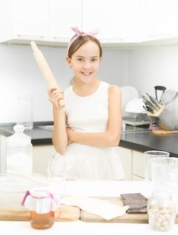 Portrait d'une adolescente mignonne posant avec un rouleau à pâtisserie en bois dans la cuisine