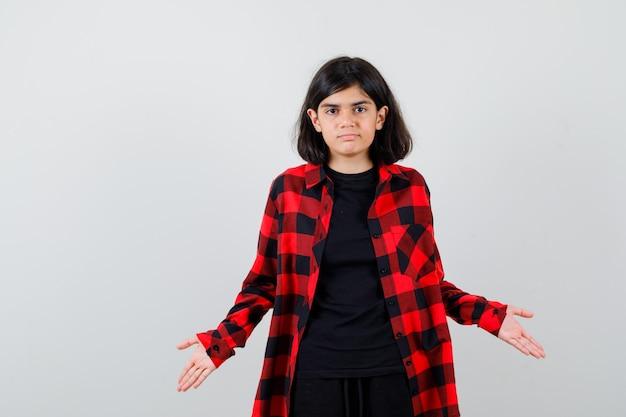 Portrait d'une adolescente montrant un geste impuissant en chemise décontractée et à la vue de face perplexe