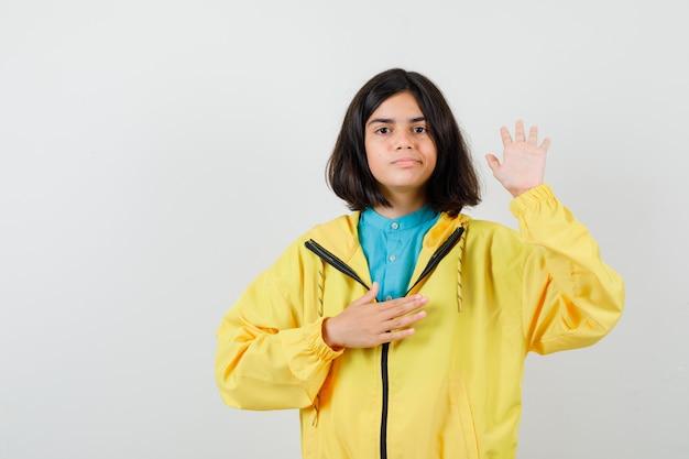 Portrait d'une adolescente montrant la paume, tenant la main sur la poitrine en veste jaune et regardant la vue de face confiante