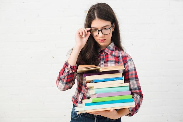 Portrait d'adolescente avec une pile de livres