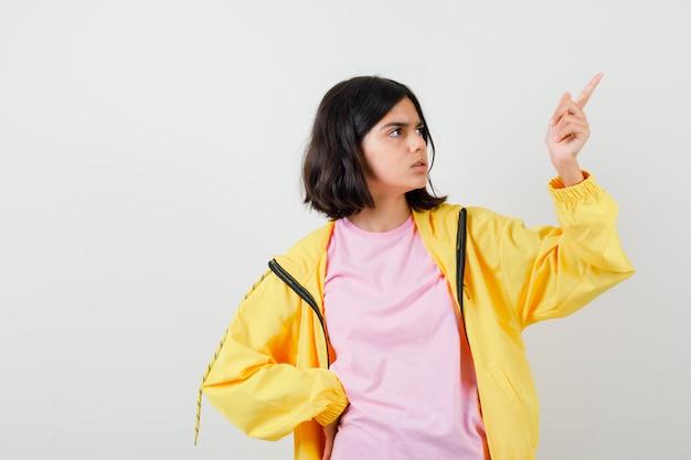 Portrait d'une adolescente pointant vers le coin supérieur droit en t-shirt, veste et à la vue de face perplexe