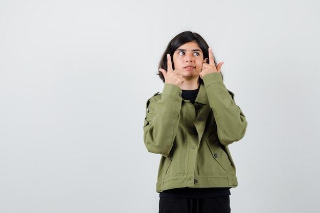 Portrait d'une adolescente pointant vers le haut, regardant vers le haut en veste verte de l'armée et regardant curieuse vue de face