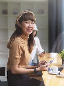 Portrait d'adolescente à la recherche dans la caméra tout en faisant la cession au café