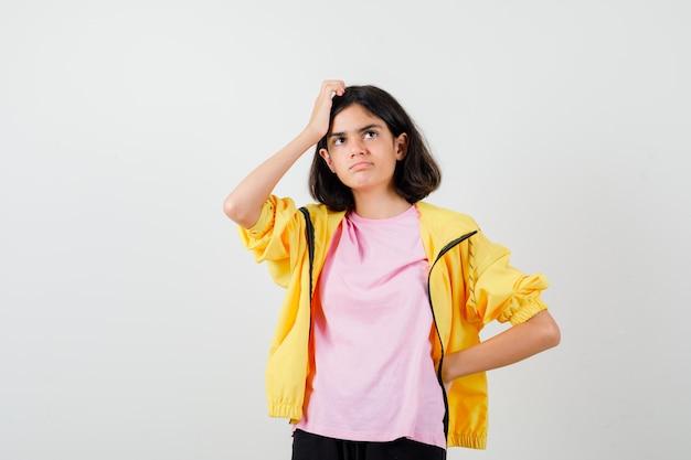 Portrait d'une adolescente se grattant la tête, regardant loin en t-shirt, veste et regardant pensive vue de face