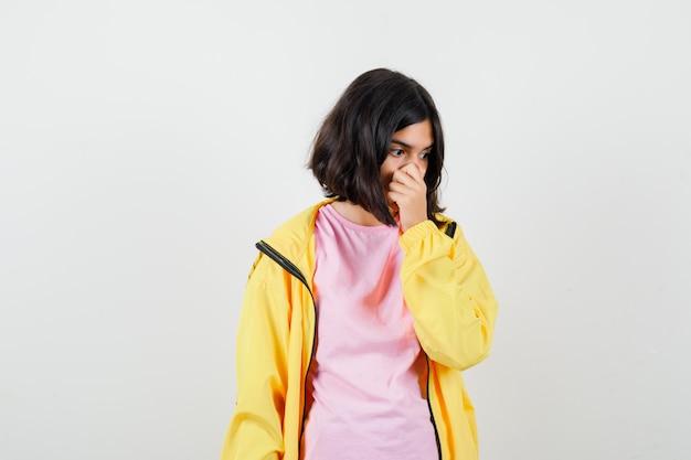 Portrait d'une adolescente se pinçant le nez tout en regardant de côté en t-shirt, veste et à la vue de face choquée