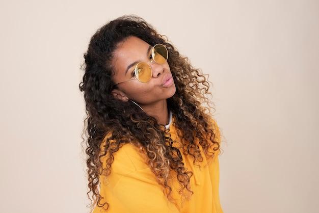 Portrait d'une adolescente souriante portant des lunettes de soleil