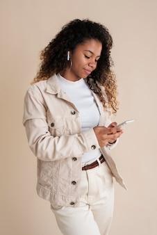 Portrait d'une adolescente souriante utilisant un smartphone