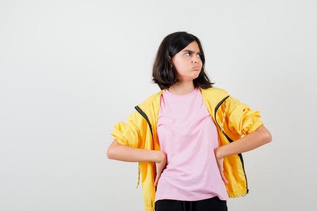Portrait d'une adolescente tenant la main sur la taille en t-shirt, veste et à la vue de face grincheuse