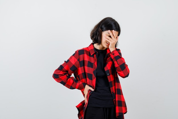Portrait d'une adolescente tenant la main sur le visage, gardant la main sur la taille en chemise décontractée et regardant la vue de face épuisée