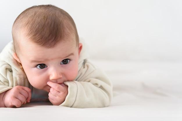 Portrait d'un adorable bébé souriant mordant ses propres doigts en mettant son poing dans sa bouche.