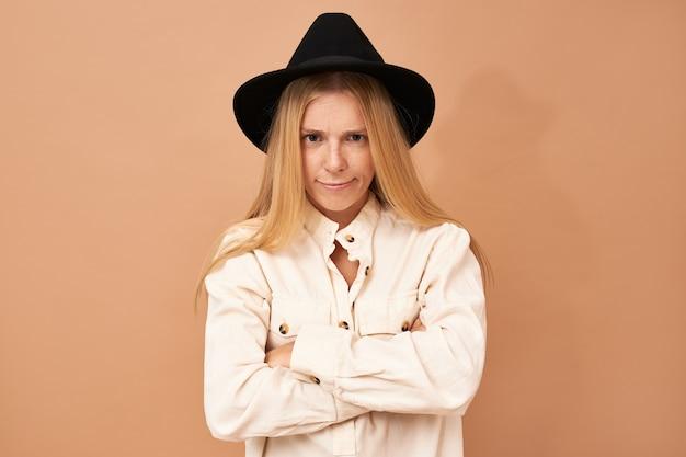 Portrait d'adorable charmante jeune femme de race blanche portant un chapeau noir posant isolé dans une posture déterminée confiante en gardant les mains sur sa taille, souriant largement