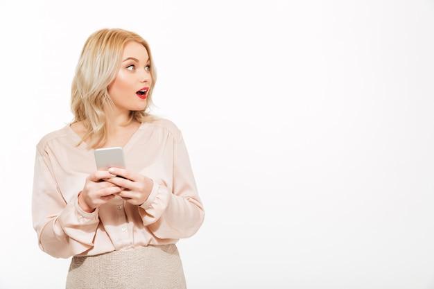 Portrait de l'adorable femme excitée aux cheveux blonds tenant le smartphone dans les mains et regardant de côté, isolé sur un espace papier peint blanc