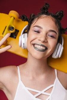 Portrait d'une adorable fille punk avec une coiffure bizarre et un rouge à lèvres foncé tenant une planche à roulettes tout en écoutant de la musique avec des écouteurs isolés sur un mur rouge
