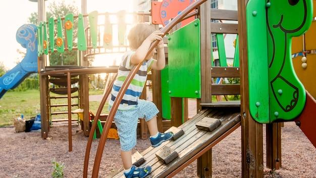 Portrait d'un adorable garçon de 3 ans grimpant sur une échelle sur le terrain de jeux pour enfants du parc
