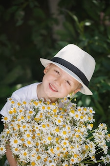 Portrait adorable garçon au chapeau avec gros bouquet blanc de marguerites