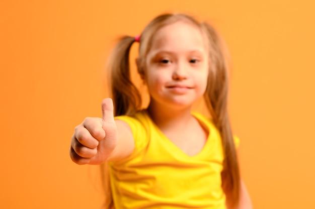 Portrait de l'adorable jeune fille avec les pouces vers le haut