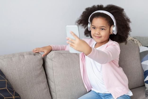 Portrait de l'adorable jeune fille prenant un selfie