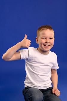 Portrait de l'adorable jeune garçon avec le pouce vers le haut