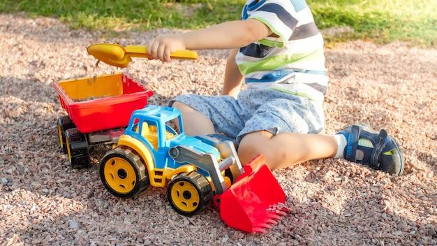 Portrait d'un adorable petit garçon de 3 ans jouant avec un camion jouet avec une remorque sur l'aire de jeux du parc