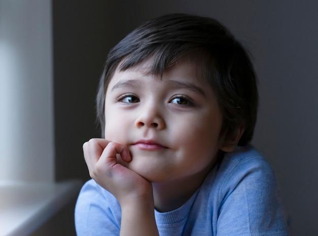 Portrait d'un adorable petit garçon assis seul et regardant la caméra avec un visage souriant
