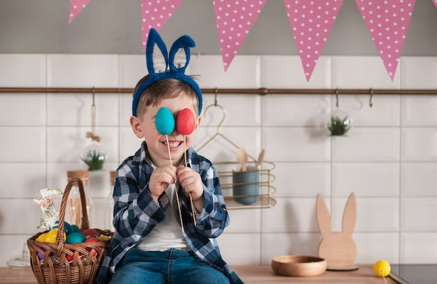 Portrait de l'adorable petit garçon tenant des oeufs de pâques