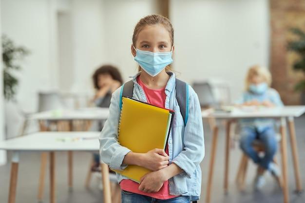 Portrait d'une adorable petite écolière portant un masque pour empêcher la propagation du covid en regardant