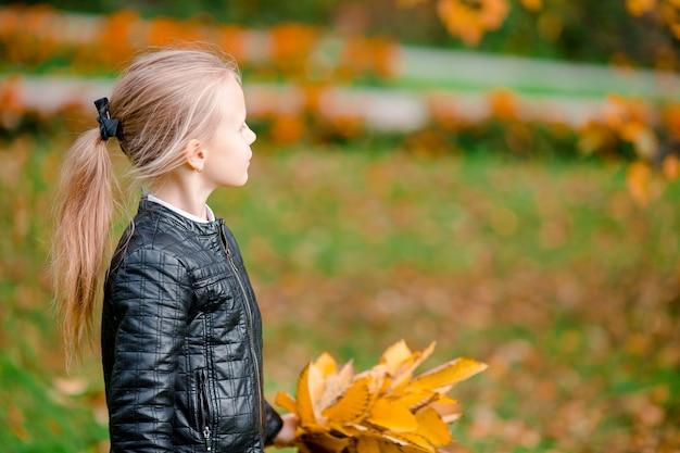 Portrait d'une adorable petite fille avec un bouquet de feuilles jaunes en automne en scooter