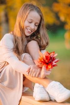 Portrait d'une adorable petite fille avec un bouquet de feuilles jaunes en automne
