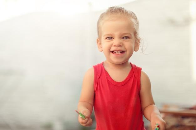 Portrait de l'adorable petite fille caucasienne montrant les dents de devant avec un grand sourire