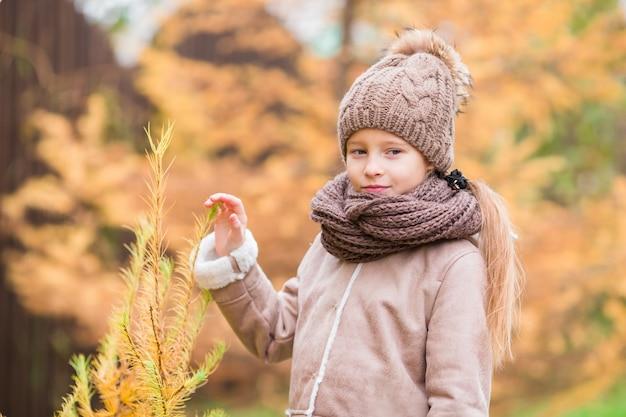 Portrait de l'adorable petite fille en plein air au beau jour d'automne