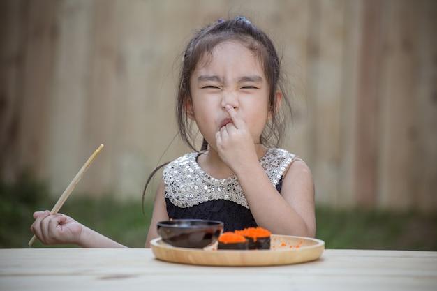 Portrait de l'adorable petite fille se sentir heureux de manger des sushis