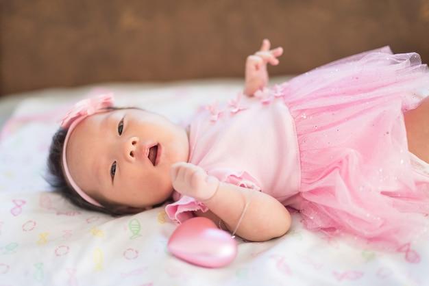 Portrait d'adorable sourire nouveau-né asiatique, 1 à 2 mois, avec une robe rose