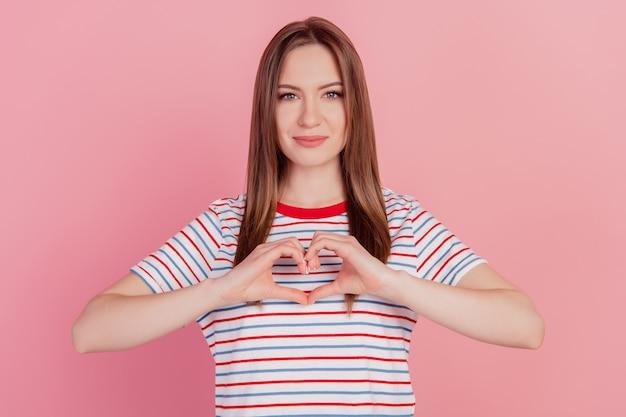 Portrait d'adorables doigts de dame affectueux montrent le symbole du coeur de geste d'amour sur fond rose