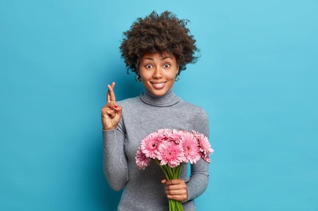 Portrait d'un afro-américain positif croise les doigts croit que les rêves deviennent réalité tient un bouquet de gerberas roses