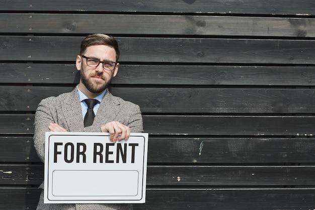 Portrait d'agent immobilier barbu mature à lunettes tenant une pancarte à louer contre le mur noir à l'extérieur