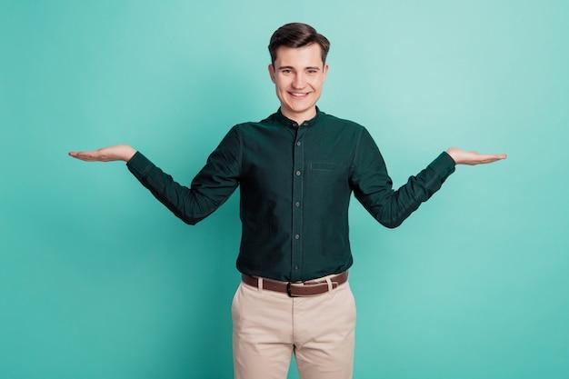 Portrait d'un agent de vente homme démontrer annonce peser les mains fond turquoise isolé