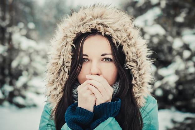 Portrait agrandi d'hiver en plein air de jeune brune heureuse. femme en manteau d'hiver au soleil