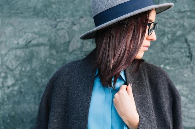 Portrait agrandi de ville élégante jeune femme à la mode sur mur gris. cheveux bruns, lunettes noires, chemise bleue, manteau gris et chapeau. perspectives élégantes, vraies émotions, regardant de côté.