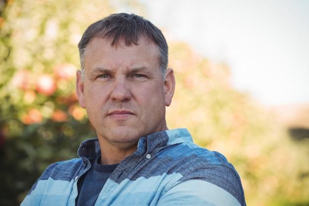 Portrait d'agriculteur debout dans un verger de pommiers